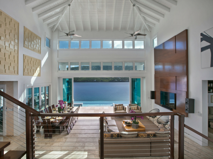 This contemporary entrance of this St. Thomas vacation home on Magen's Bay has a 45' tall ceiling with a view of an infinity pool and the bay beyond that. Innovate Building Solutions