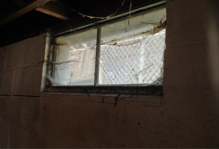 Nasty cobweb infested metal framed basement window which will be replaced with a glass block window - Innovate Building Solutions
