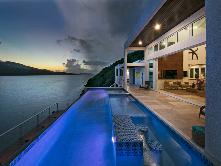 Nightime view of an infinity pool with LED lighting at a contemporary St. Thomas vacation home overlooking Magen's Bay - Innovate Building Solutions
