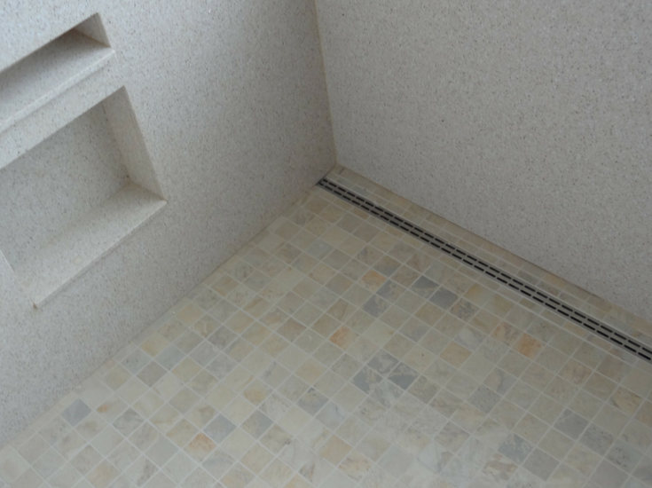 A linear drain system in a roll in shower floor pan | Innovate Building Solutions