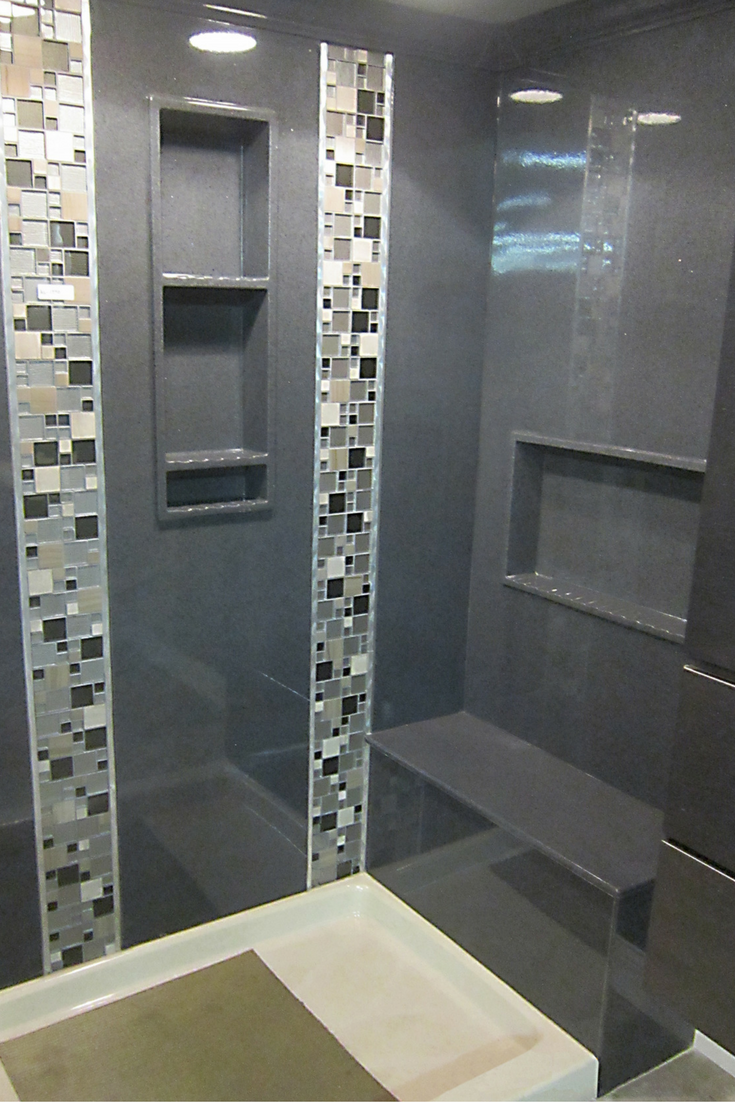 Gray colored cultured marble solid surface shower panels with a decorative vertical tile strip border - Innovate Building Solutions