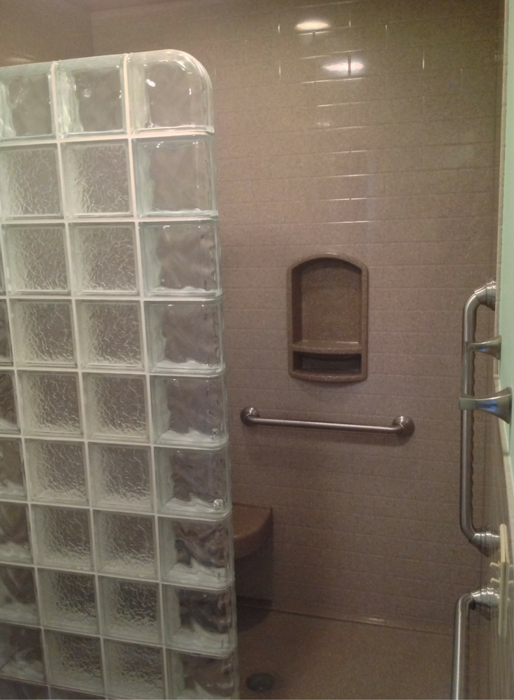 Low profile solid surface shower pan and wall panels with grab bars in an accessible shower | Innovate Building Solutions