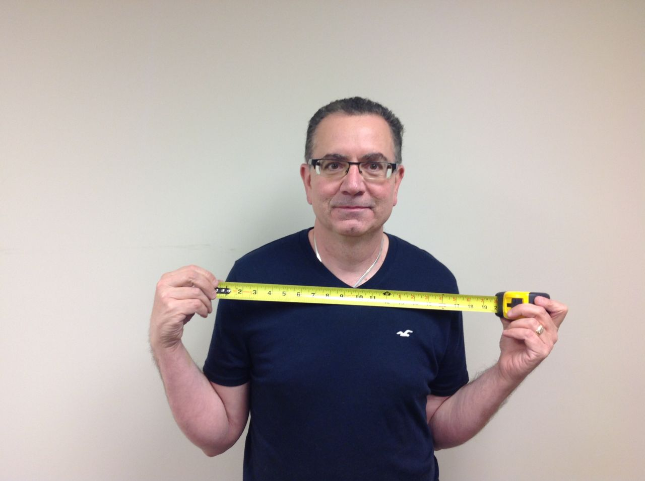 Mike Foti of Innovate Building Solutions measuring his personal width to determine the size of a shower opening