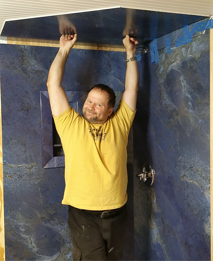 Raul Bajuski of The Tiny House Escape installing faux marble grout free shower wall panels. This is a top 10 blog post of 2016 from The Innovate Building Solutions remodeling blog.