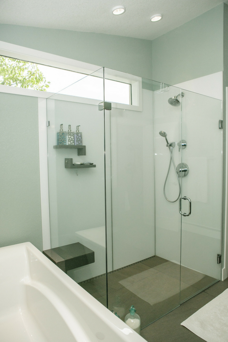 A contemporary high gloss shower wall panels system in an upscale bathroom remodeling project with a clear frameless glass enclosure system | Innovate Building Solutions