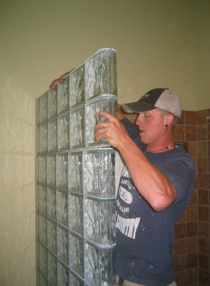 """A glass block shower wall being installed with prefabricated sections which fit together like """"Lego"""" blocks 