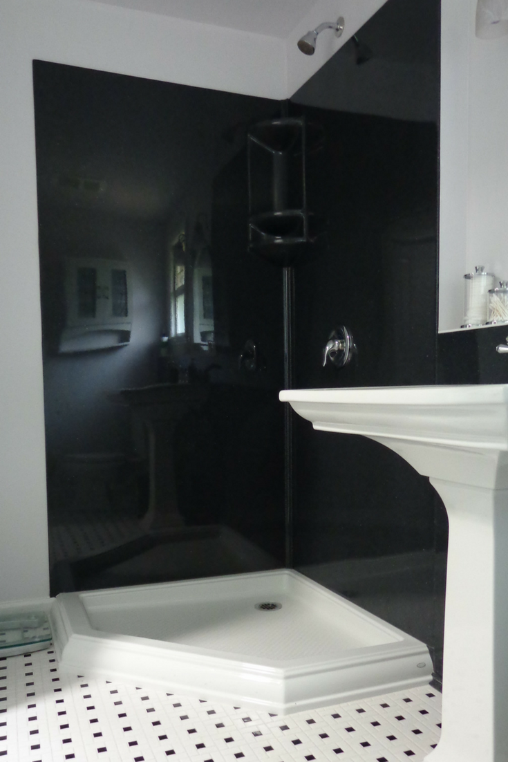 Black colored smooth solid surface shower wall panels in a corner shower - Innovate Building Solutions