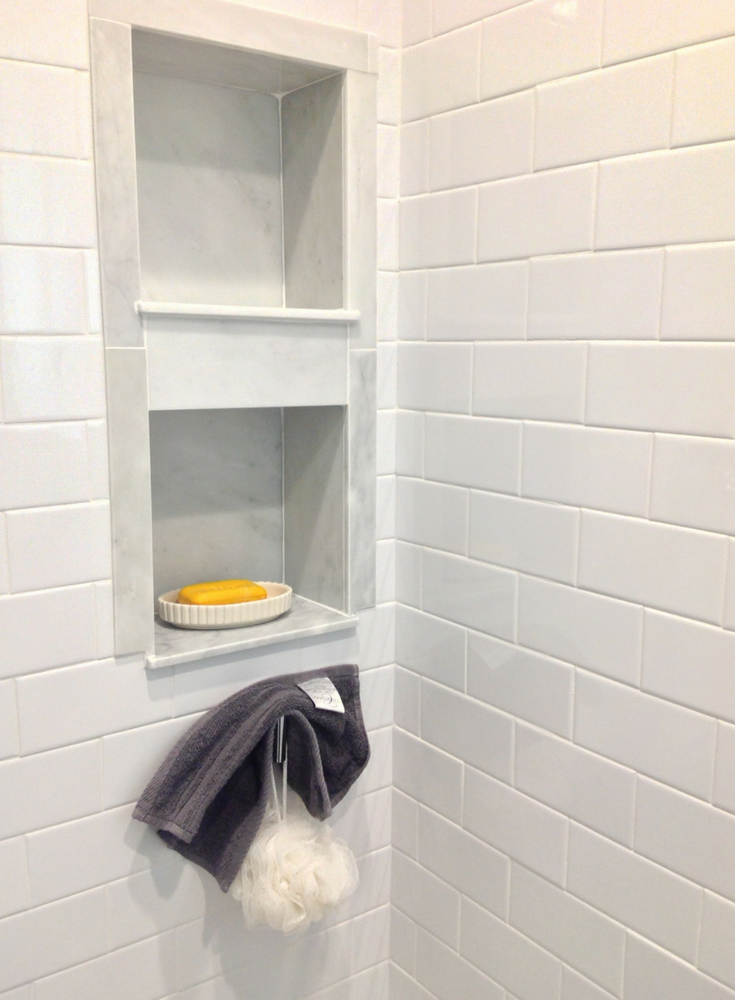 Solid surface subway tile wall panels with a marble recessed niche - Innovate Building Solutions