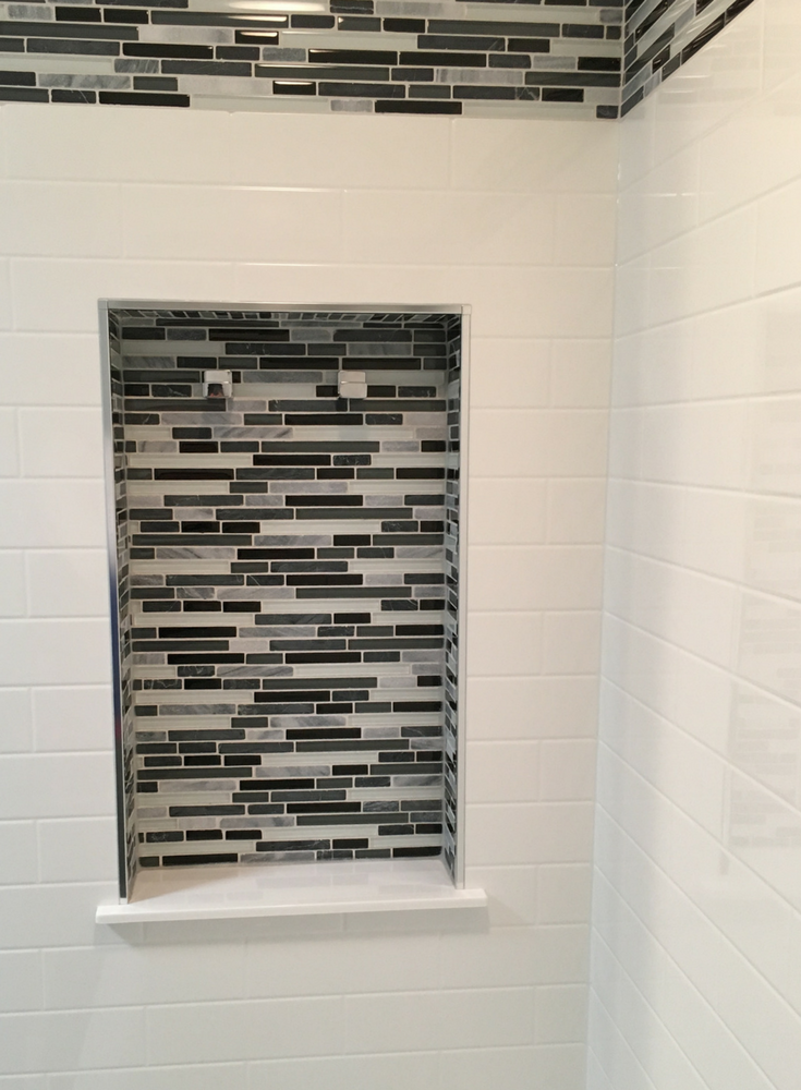 Tile shower niche inside of a solid surface subway tile shower wall surrounds | Innovate Building Solutions
