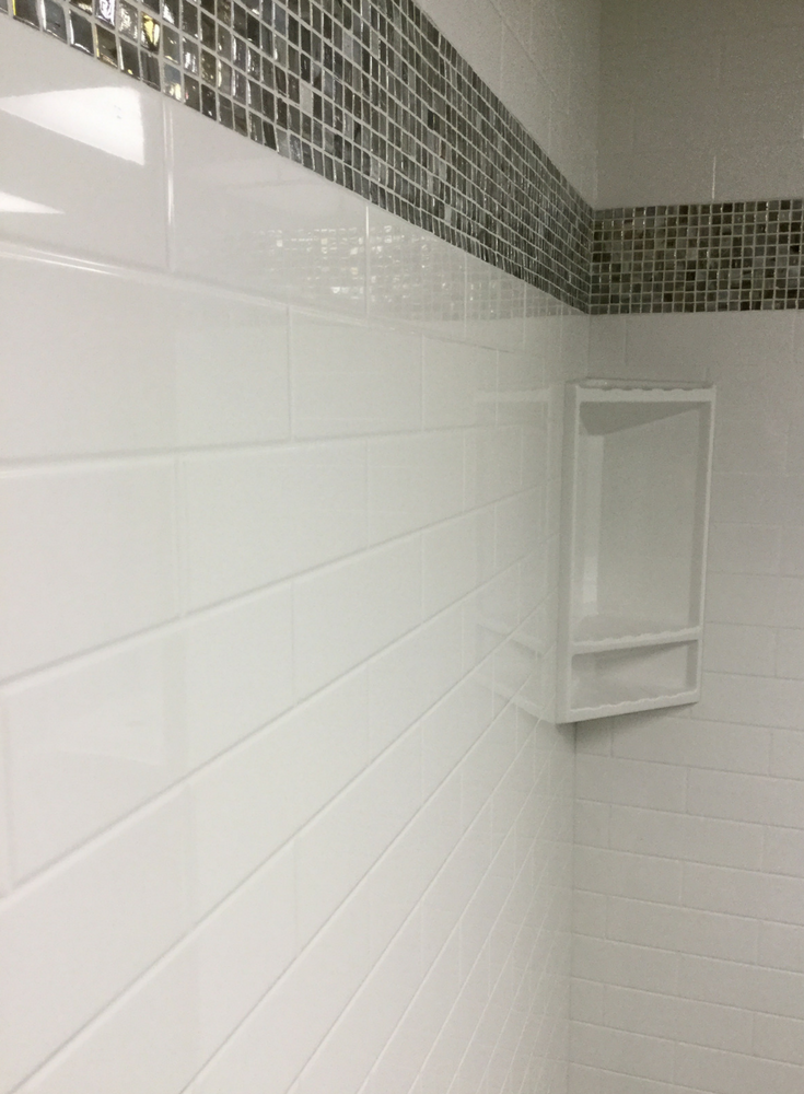 A multicolored glass tile border in a solid surface wall with a subway tile pattern | Innovate Building Solutions
