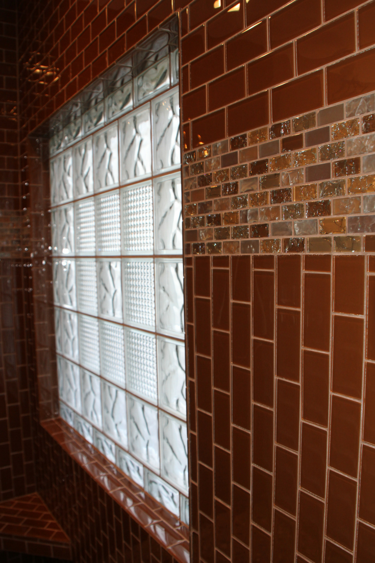 Ceramic tiles return back to a glass block to trim this window | Innovate Building Solutions