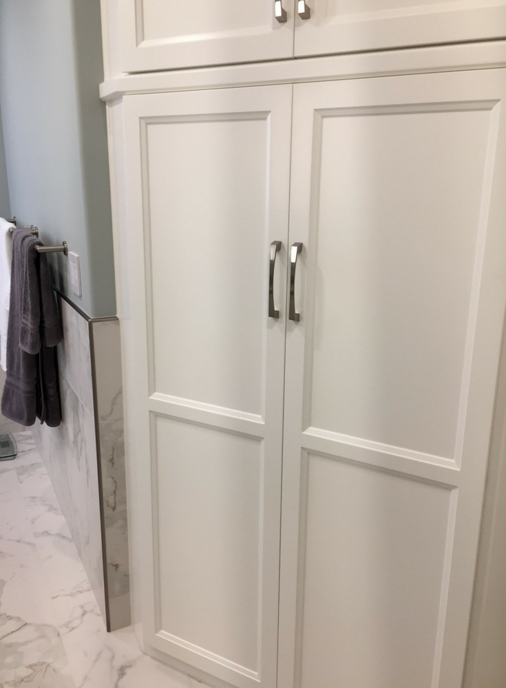 Custom angled shaker style linen cabinet in a bathroom remodel for extra storage - Innovate Building Solutions