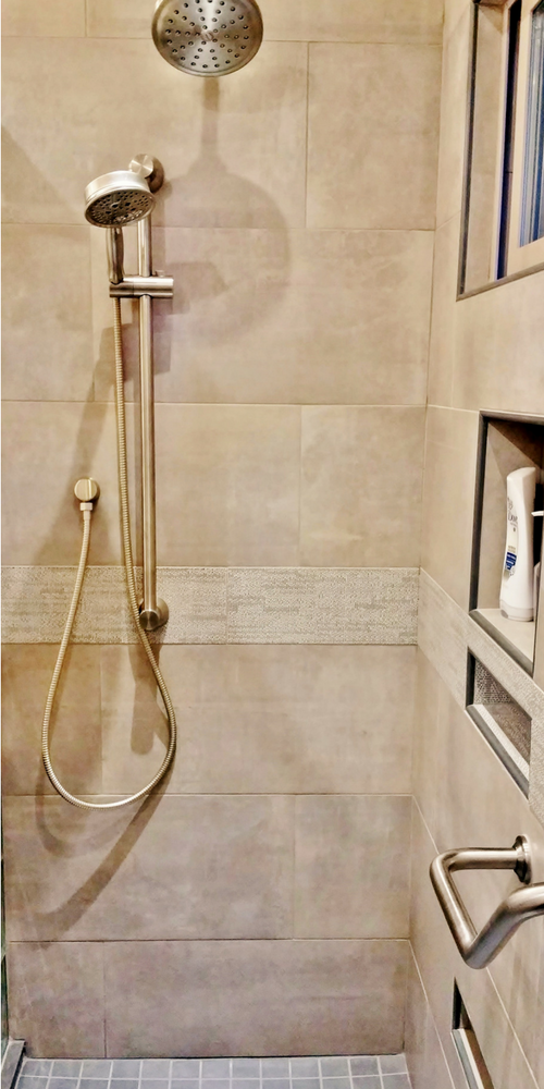 Earth tone colors create a relaxing tile shower stall in this bathroom remodeling in a vacation home in Cazadero California - Innovate Building Solutions