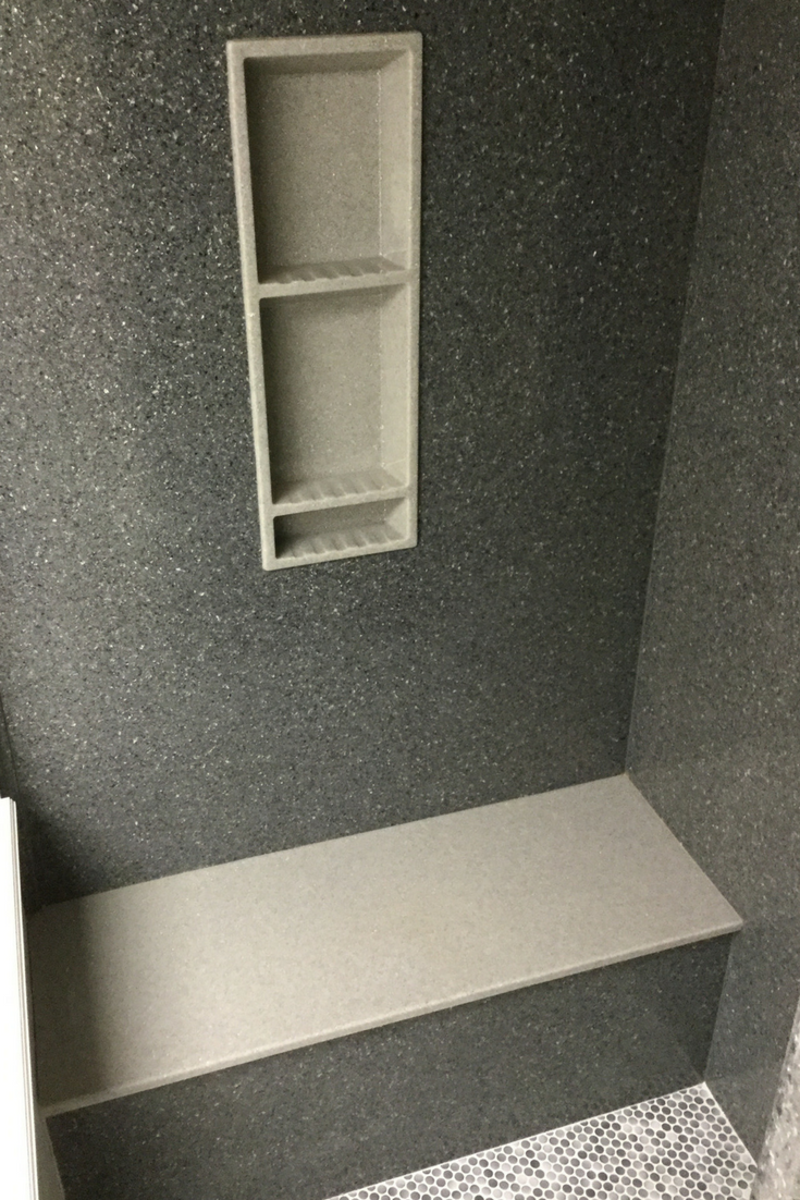 Solid surface slate texture shower walls with a different colored niche and bench seat | Innovate Building Solutions