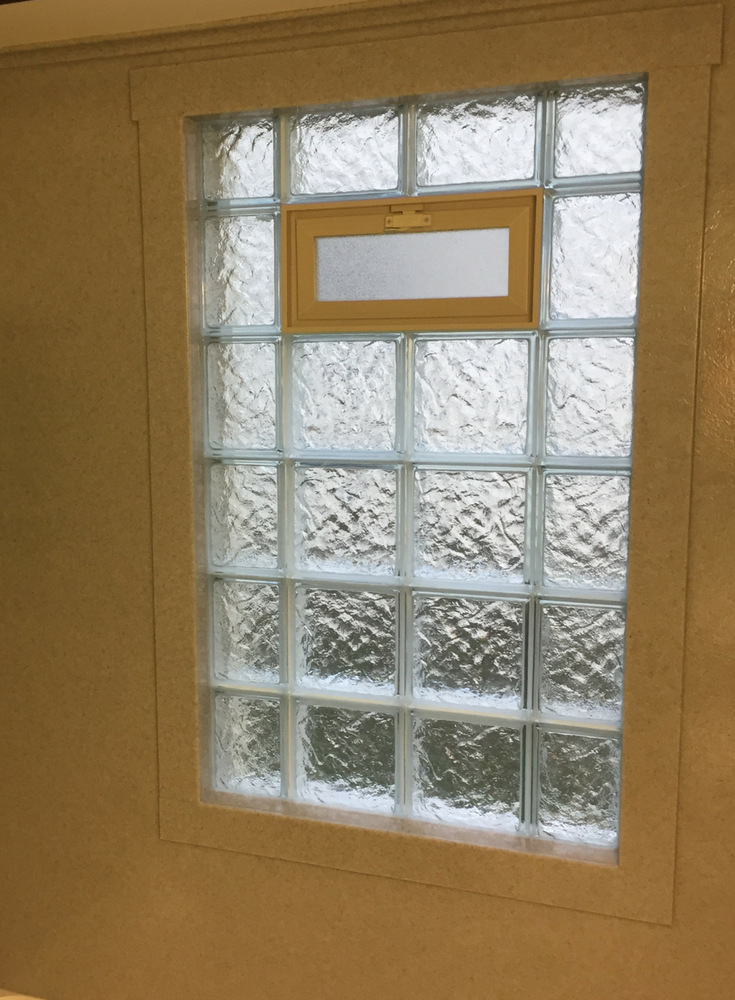Solid surface window shower trim around a glass block vented window | Innovate Building Solutions