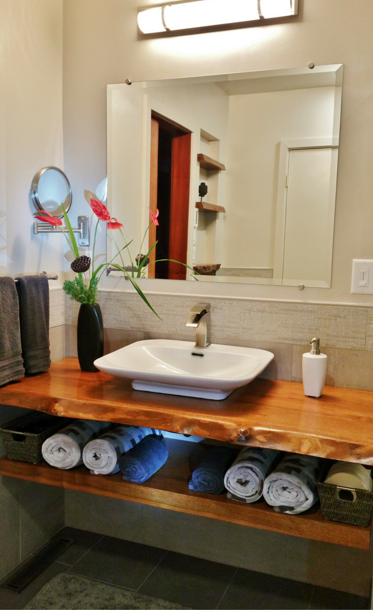 This vanity countertop was made from a bay laurel tree and stained and varnished to bring the outdoors into this bathroom. It was used in a zen-inspired bathroom remodel - Innovate Building Solutions