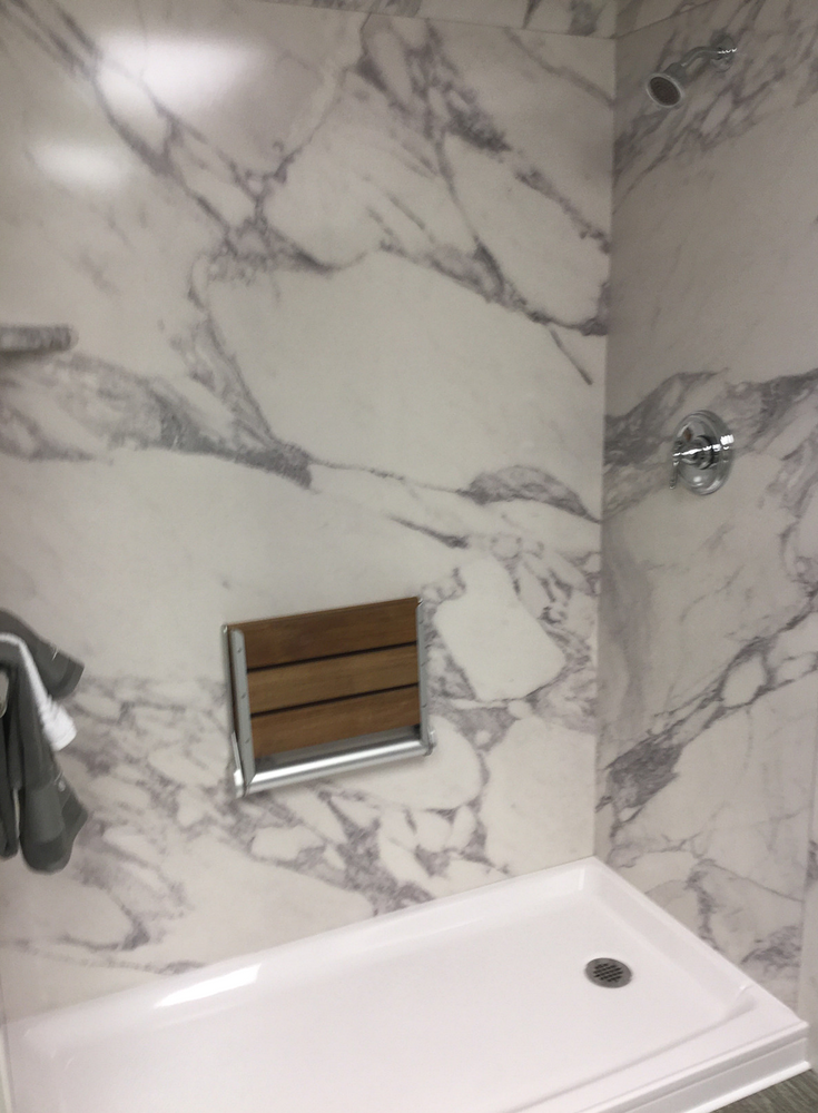 Faux marble calcutta white shower wall panels with an acrylic shower pan and a fold down teak shower seat | Innovate Building Solutions