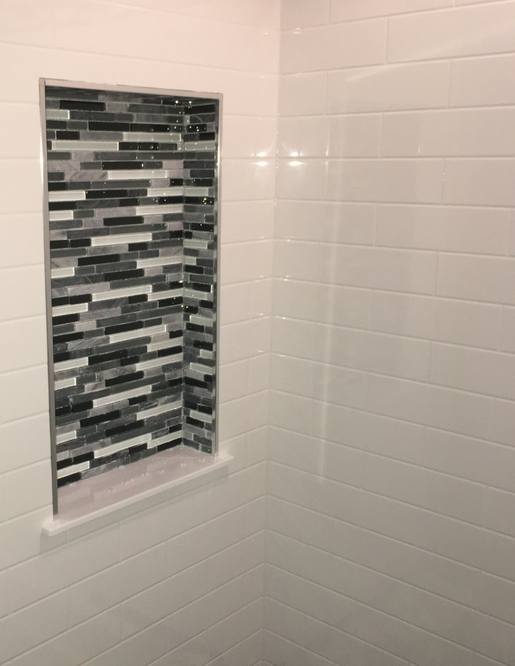 Solid surface grout free shower panels and glass tile recessed niche | Innovate Building Solutions