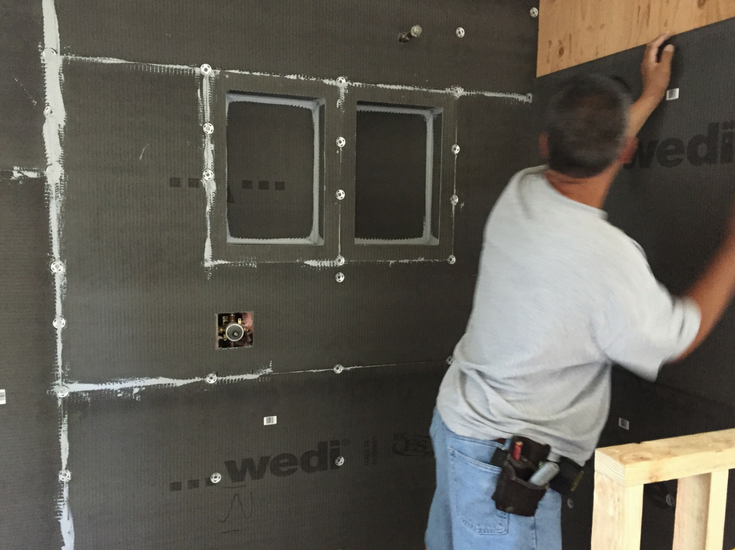Wedi waterproof wall backer board panels being installed behind a tile shower | Innovate Building Solutions
