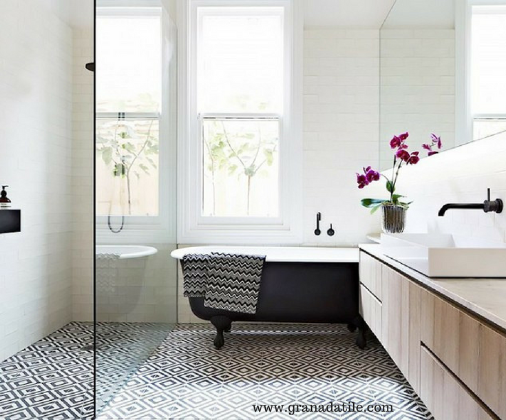 A geometric bathroom tile design in a bathroom with a one level contemporary shower and a clawfoot tub | Innovate Building Solutions