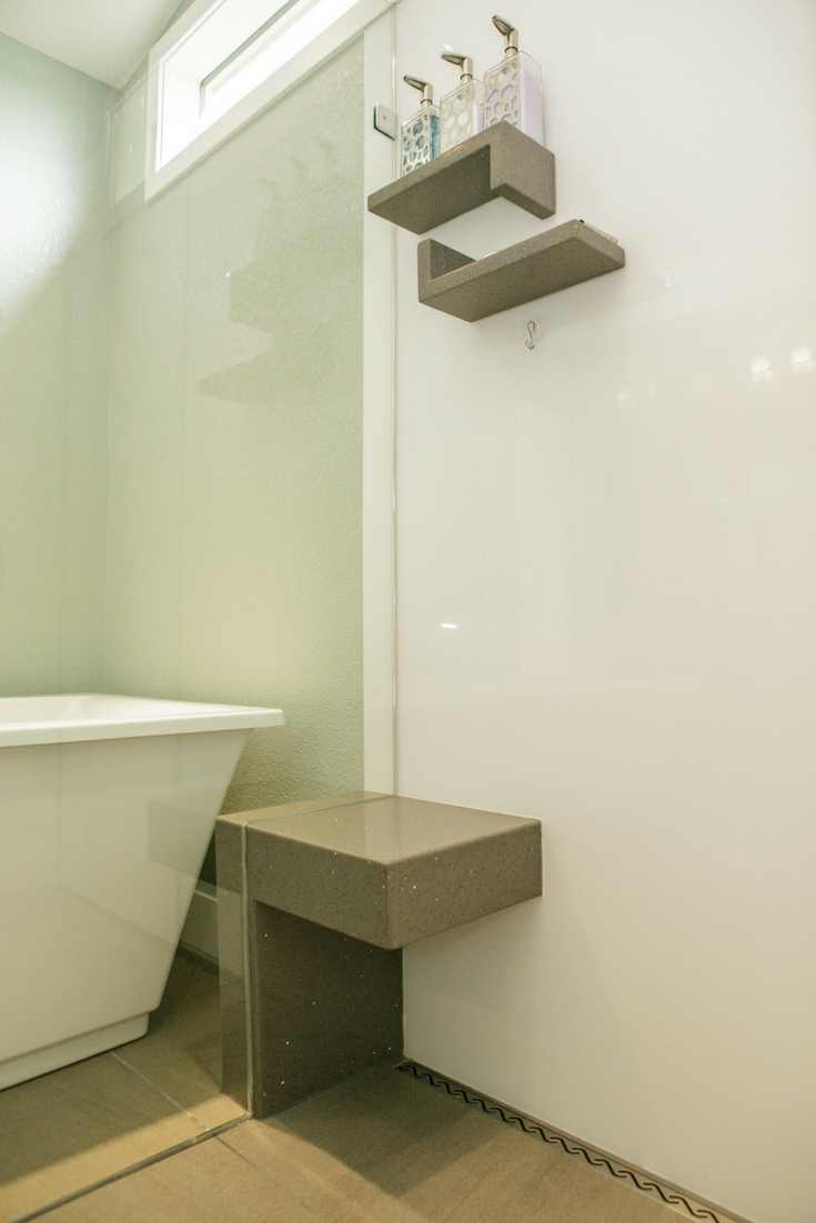 Contemporary luxury high gloss shower wall panels in a modern bathroom with a custom bench seat which extends outside the frameless glass enclosure | Innovate Building Solutions