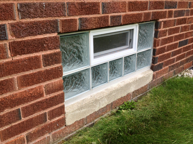 A glass block window with a high privacy iceberg pattern with an air vent mortared into a brick foundation | Innovate Building Solutions