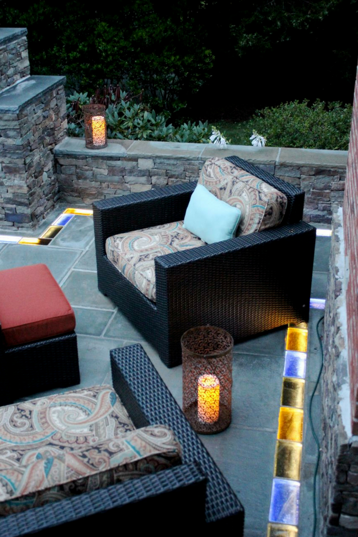 This outdoor fire pit and seating area used decorative blue stone and illuminated colored glass brick pavers for a fun and unique look! | Innovate Building Solutions