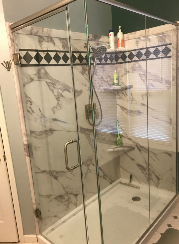 Calcutta white marble faux stone wall panels with a double threshold solid surface shower pan with a frameless 2 sided custom glass enclosure | Innovate Building Solutions