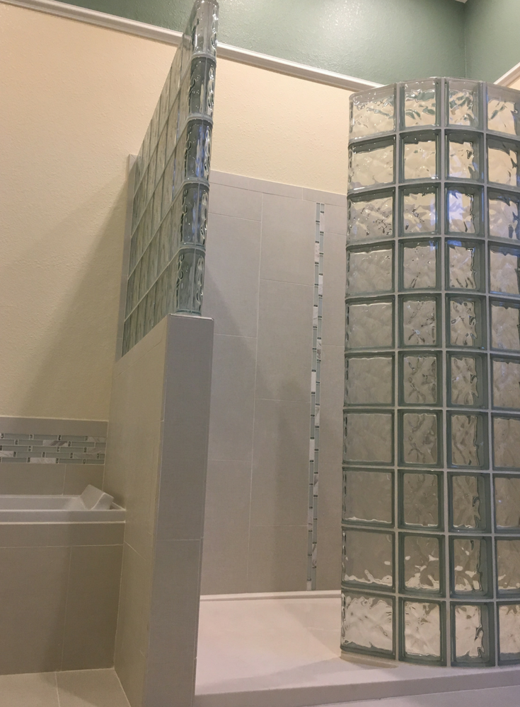 Custom shaped solid surface shower base with premanufactured glass block shower wall kit | Innovate Building Solutions