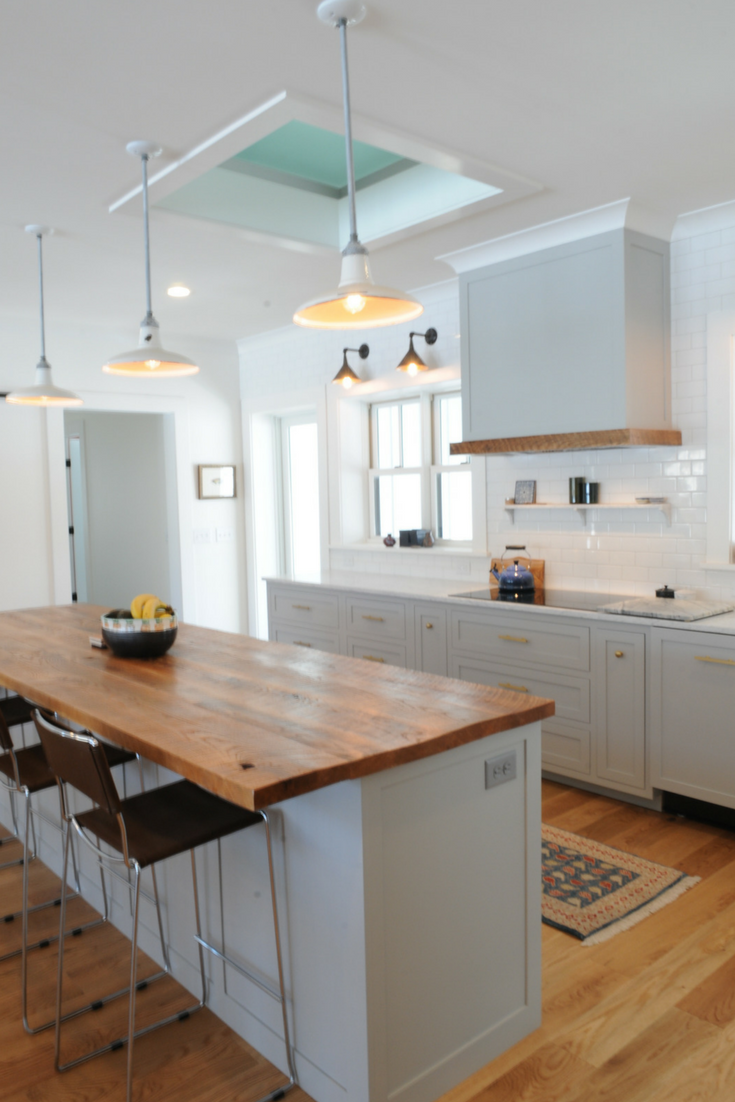 This modern farmhouse custom kitchen has an obscure glass floor panel in the ceiling which moves light into what would have been a darker space through the lofted studio above. | Innovate Building Solutions