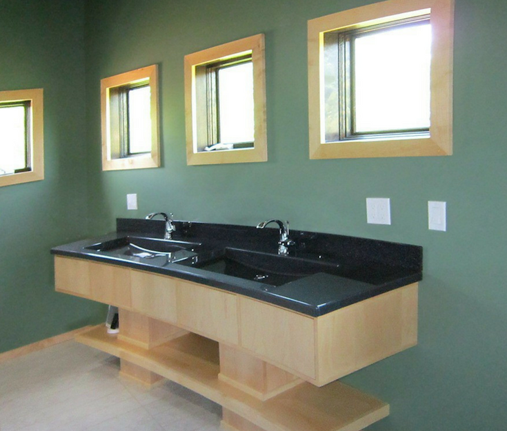 Solid surface black vanity countertop in a contemporary bathroom | Innovate Building Solutions