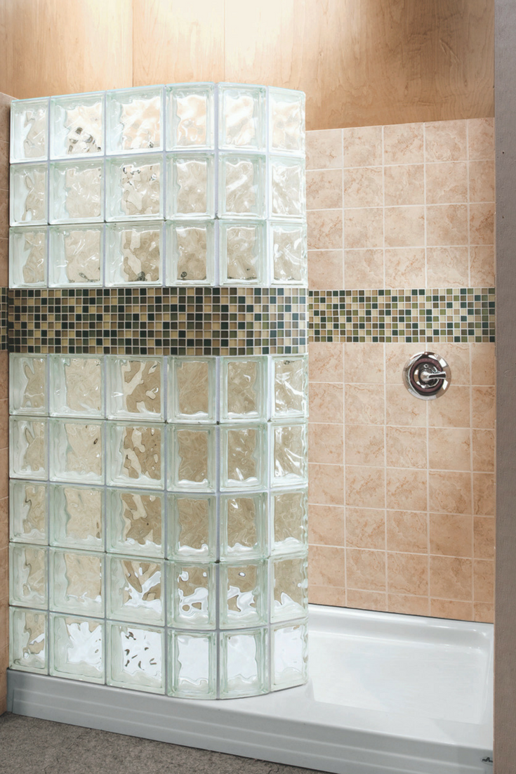 A curved glass block walk in shower wall with a decorative tile border | Innovate Building Solutions