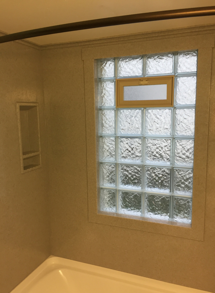 A glass block wave pattern vented window with solid surface trim for a watertight shower window | Innovate Building Solutions