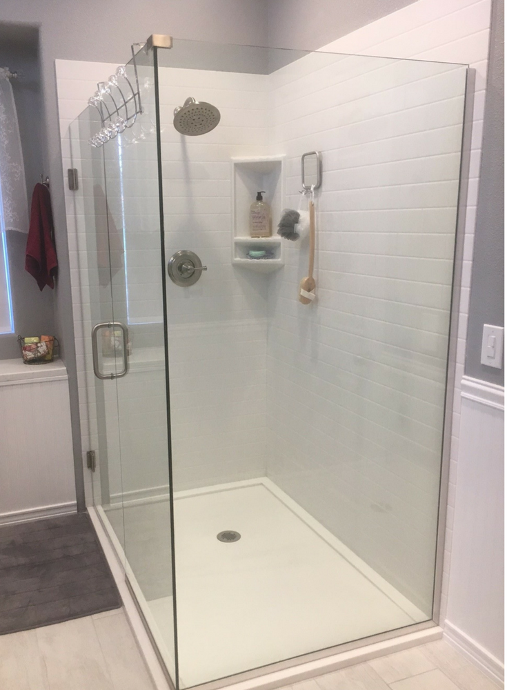 An easy to clean low curb solid surface shower floor pan in white with solid surface subway tile pattern grout free walls and a clear frameless glass enclosure | Innovate Building Solutions