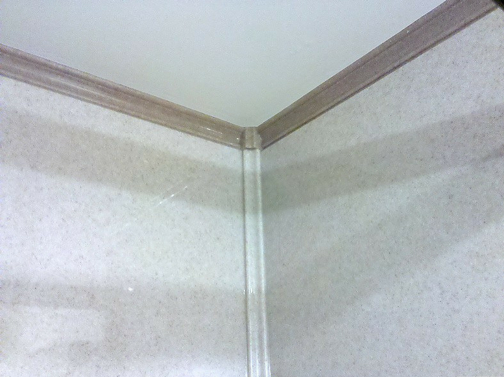 Corner trim and crown molding in a solid surface shower | Innovate Building Solutions
