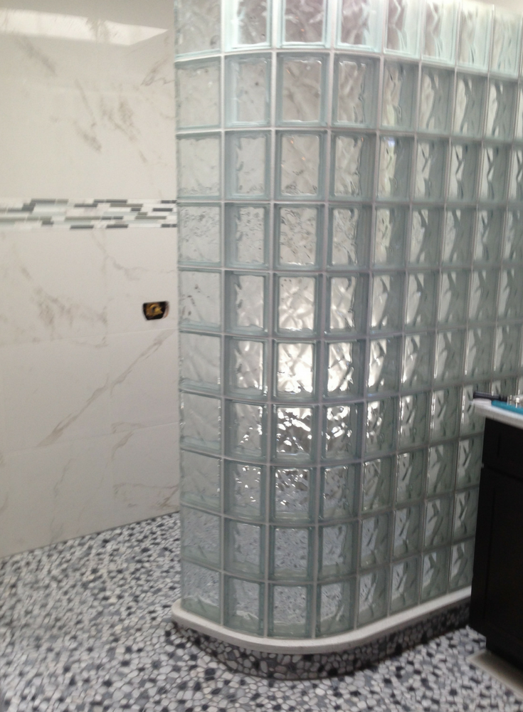 Curved glass block shower wall in a wave pattern with a premade waterproof ready for tile shower base | Innovate Building Solutions