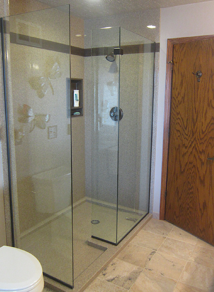 Custom sized solid surface walk in shower with a frameless glass enclosure | Innovate Building Solutions