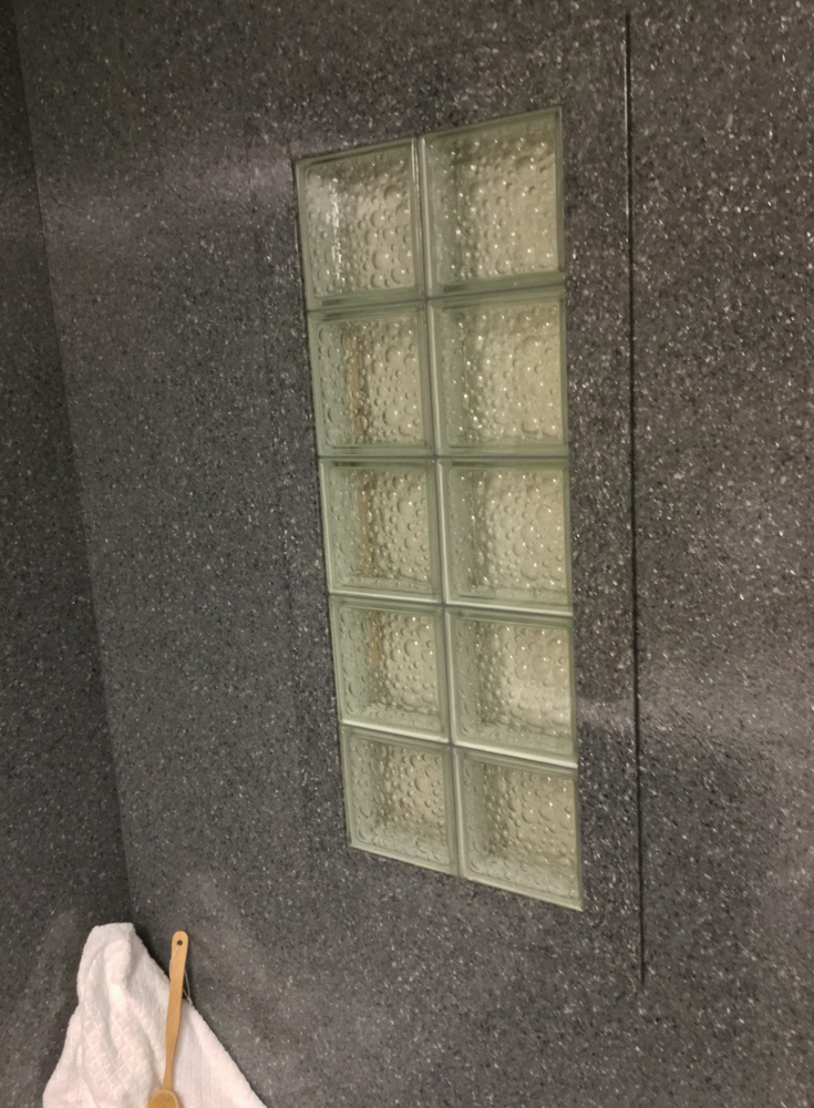 Darker colored solid surface window trim around a glass block window with a bubble pattern | Innovate Building Solutions