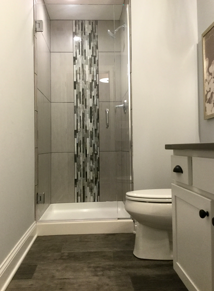 Decorative vertical tile design in a small shower enclosure | Innovate Building Solutions