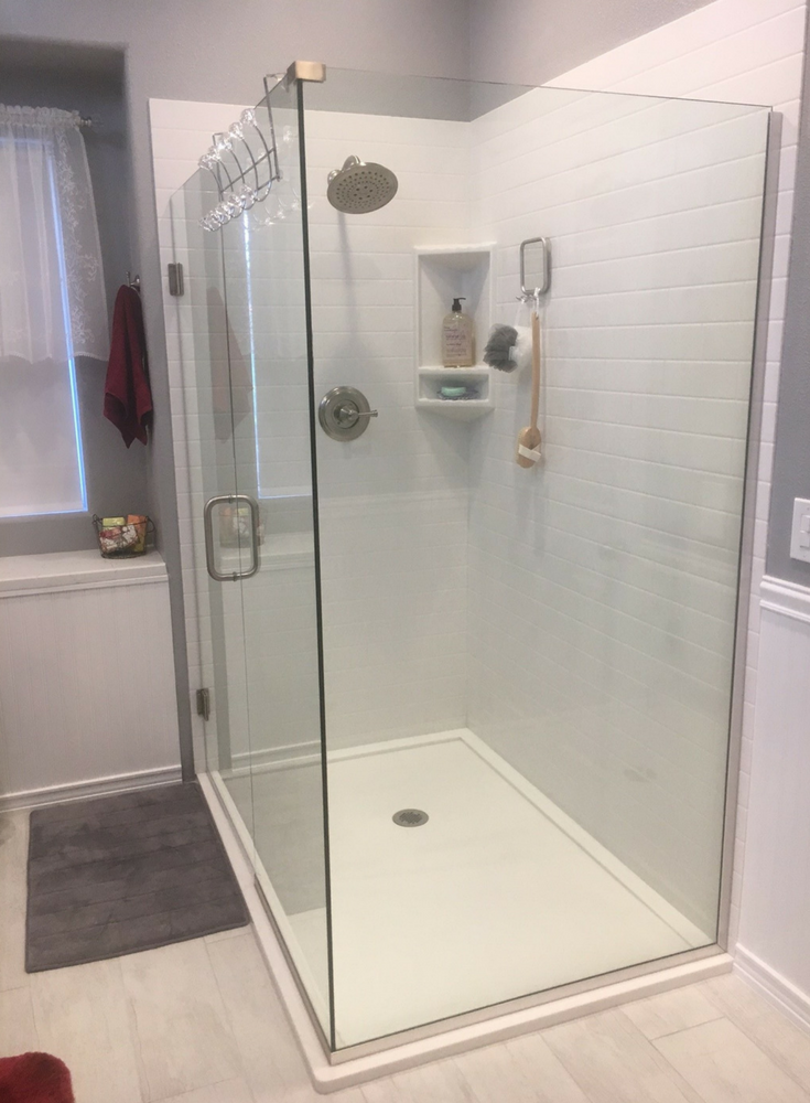 Double curb low profile white solid surface shower pan with a frameless glass | Innovate Building Solutions