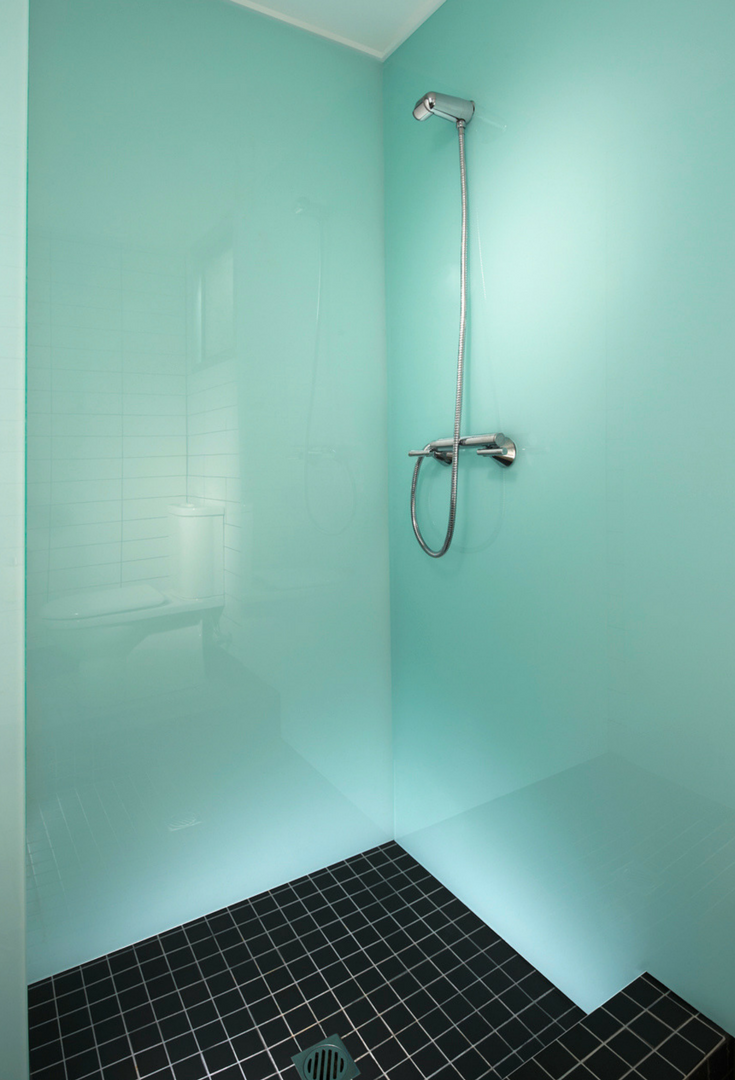 Glacier colored high gloss corner shower wall with black ceramic tile shower floor in an upscale home | Innovate Building Solutions