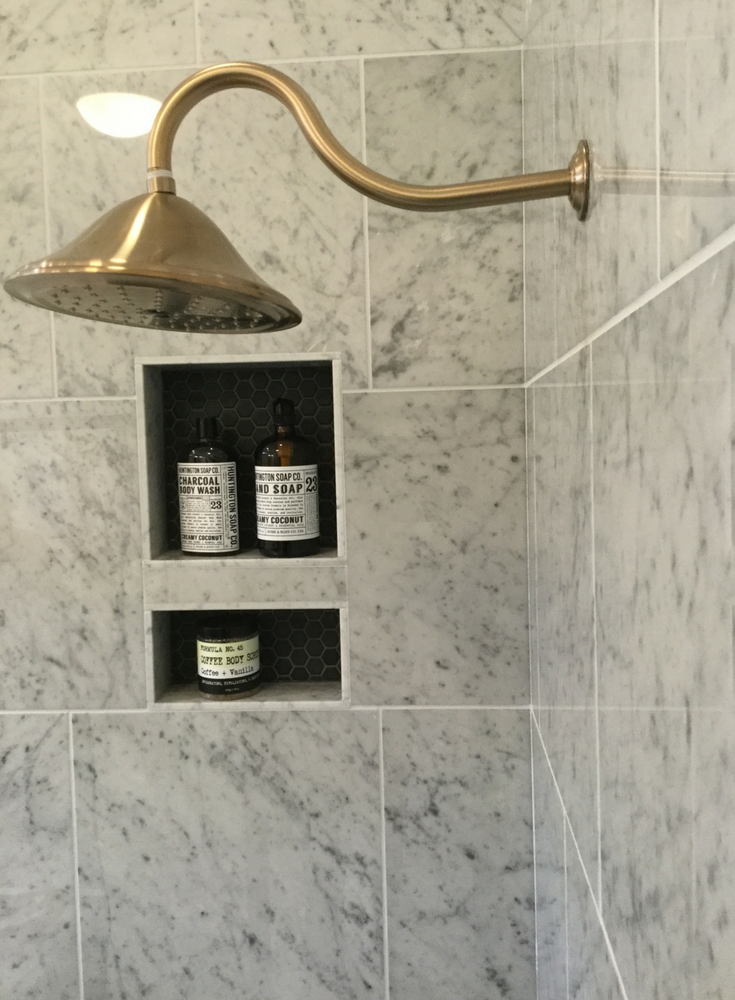 Mosaic tile recessed niche in a marble shower with a brass shower head system   Innovate Building Solutions