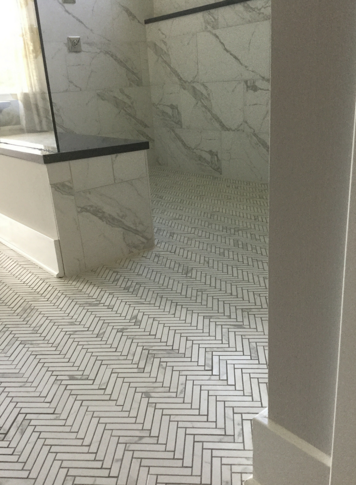 One level barrier free shower finished with a herringbone tile pattern | Innovate Building Solutions