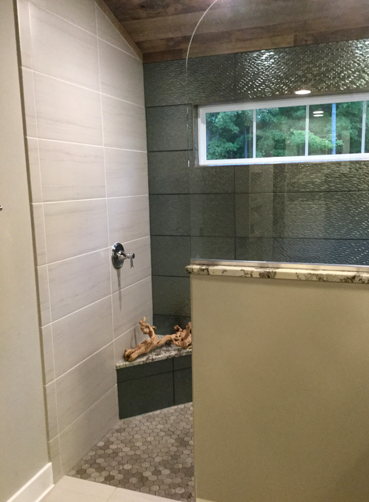 A showerr transom window and frameless glass partition help to move light into the vanity area of a bathroom   Innovate Building Solutions