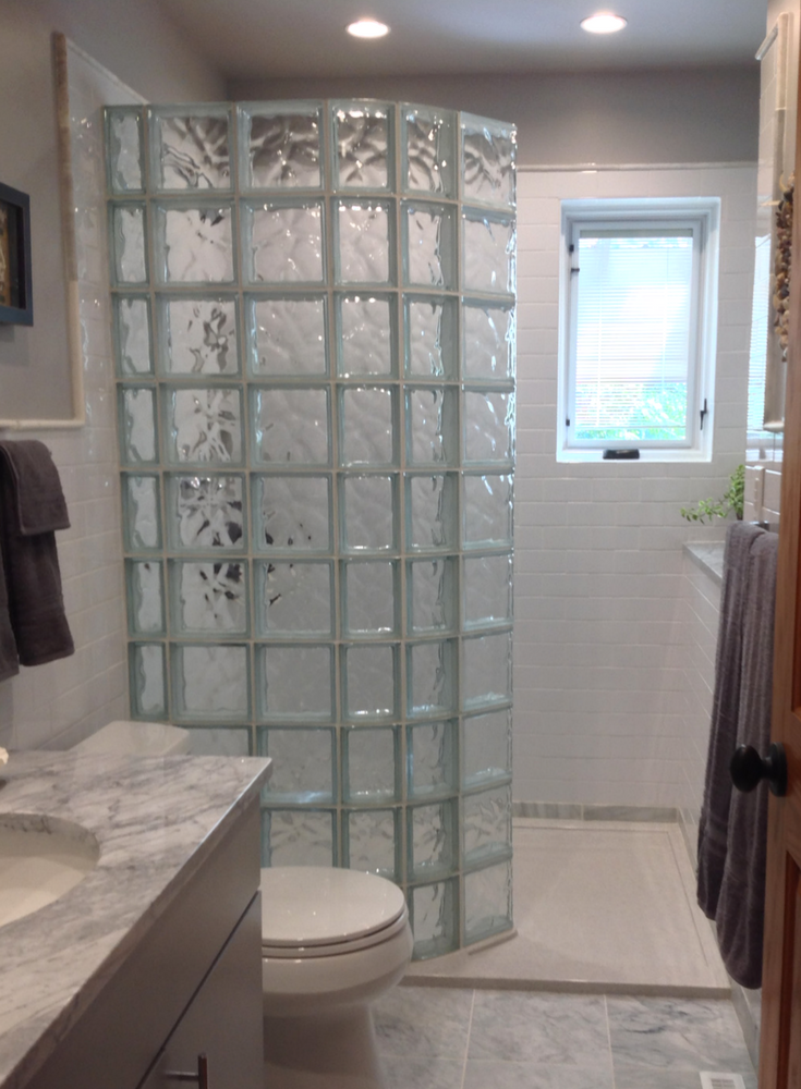 Doorless walk in curved glass block shower and stone pan