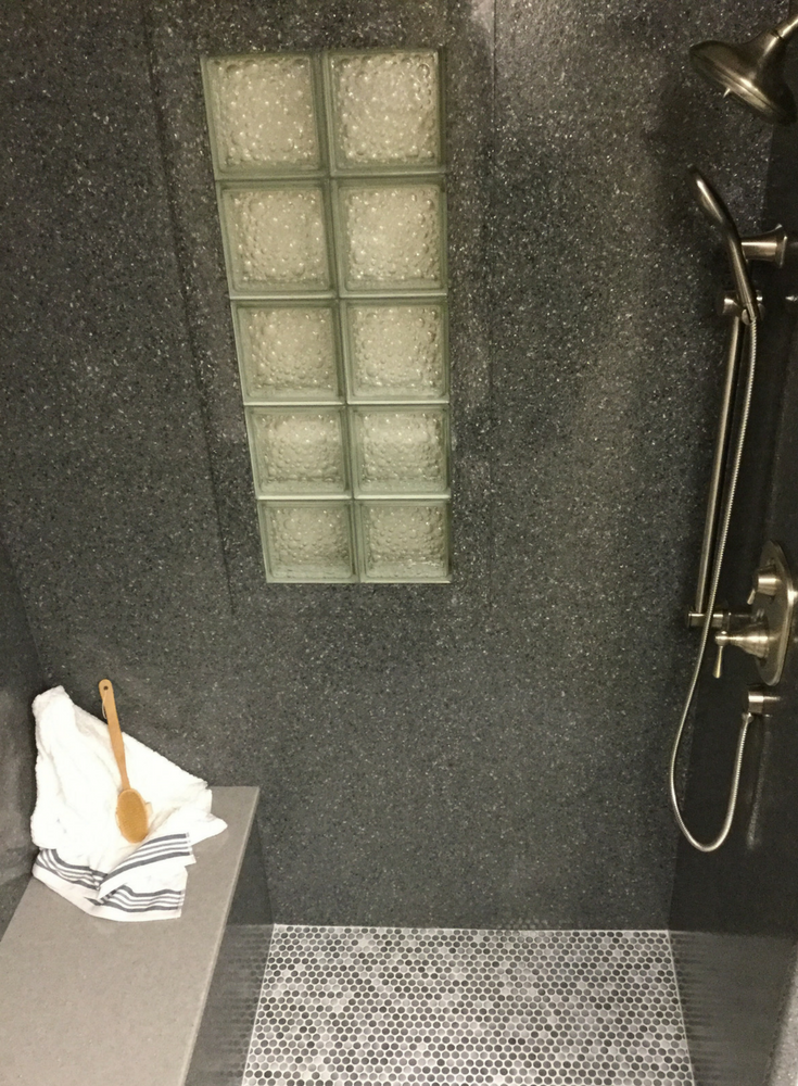 Gray solid surface shower walls and a bench seat in a slate texture with a bubble pattern glass block shower window | Innovate Building Solutions