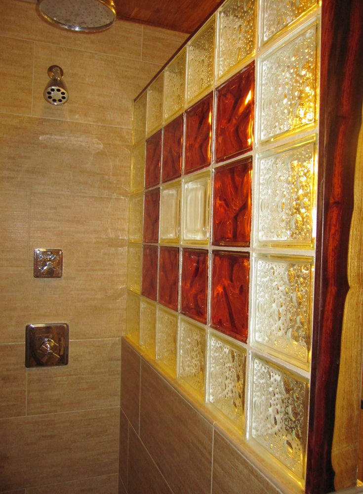 Ruby red glass blocks with a bubble pattern blocks and cocobolo wood shower trim | Innovate Building Solutions