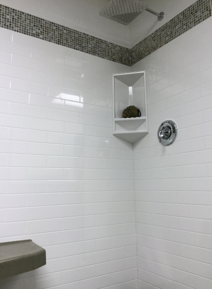 White subway tile pattern solid surface grout free shower panels with an iradescent glass tile row | Innovate Building Solutions