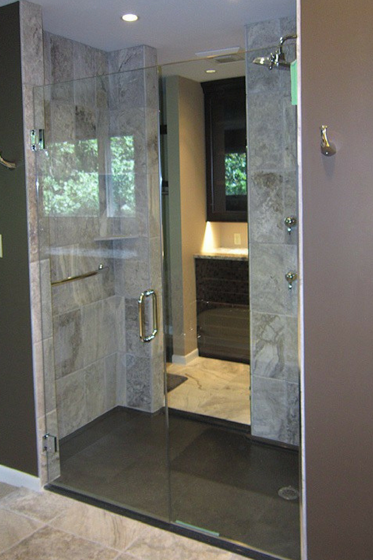 Dark brown low profile stone shower pan with a custom glass enclosure | Innovate Building Solutions