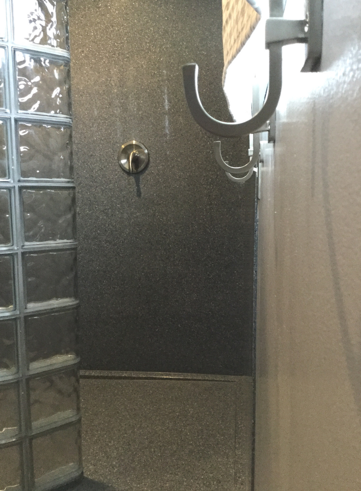 Gray colored solid surface shower wall panels in a curved glass block walk in shower | Innovate Building Solutions